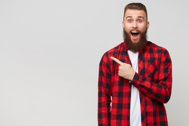 Impressed handsome young bearded guy in checkered shirt with fashion hairstyle advices something unbelievable, opened mouth because of amazement pointing with fore finger to the left, on white wall