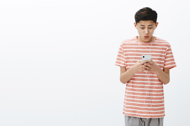Impressed happy excited attractive young asian male with cool hairstyle in striped t-shirt holding smartphone looking pleased and amazed at cellphone screen saying wow