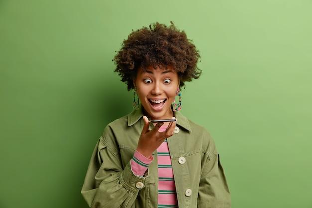 Впечатленная счастливая удивленная женщина чувствует взволнованные взгляды на дисплей смартфона, держит сотовый возле рта, отправляет голосовое сообщение, одетая в модную одежду, изолированную на зеленой стене студии