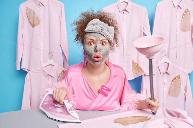 Impressed housewife stares surprised cannot believe in shocking news uses electric iron and plunger for cleaning toilet applies clay mask on face poses against ironing board. household duty concept