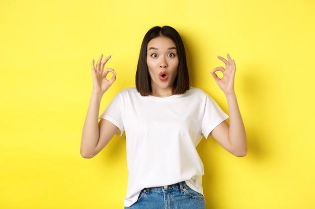 Впечатленная корейская девушка, стоящая на желтом фоне, говорит: «вау», показывает хорошие знаки и выглядит изумленно