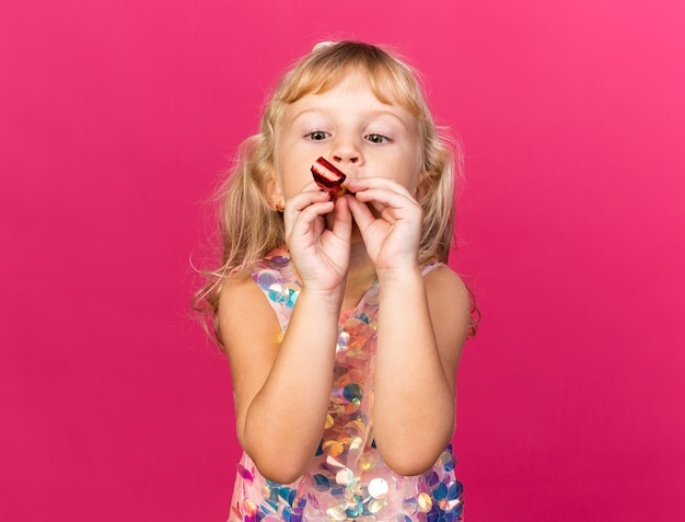 Impressed little blonde girl blowing and looking at party whistle isolated on pink wall with copy space