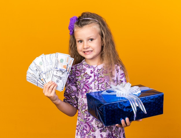 Impressed little blonde girl holding gift box and money isolated on orange wall with copy space
