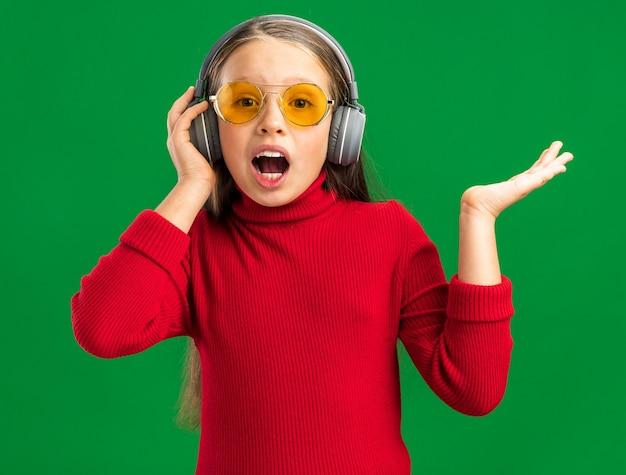 Piccola ragazza bionda impressionata che indossa le cuffie e gli occhiali da sole che afferrano le cuffie che guardano davanti con la bocca aperta isolata sulla parete verde con lo spazio della copia