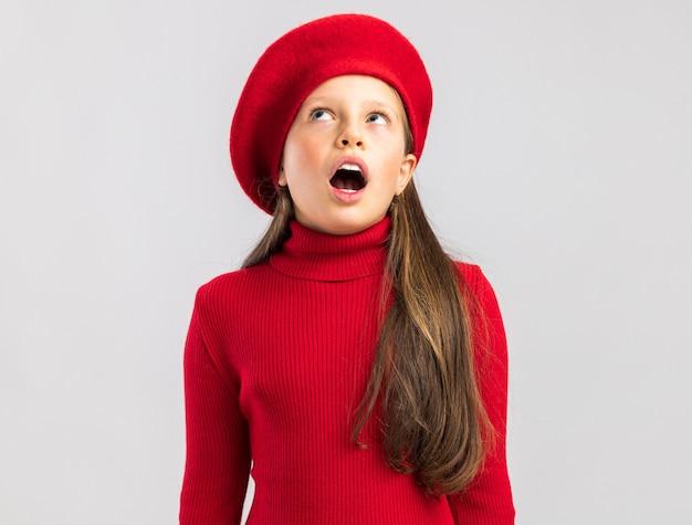 빨간 베레모를 쓴 금발 소녀가 복사공간이 있는 흰 벽에 격리된 입을 벌리고 올려다보는 것에 깊은 인상을 받았습니다.