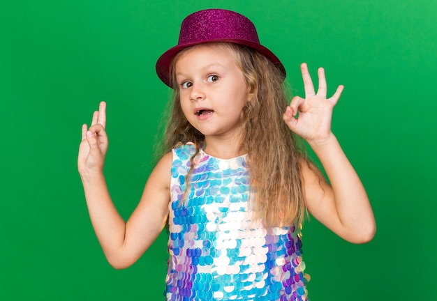 복사 공간이 녹색 벽에 고립 된 확인 서명 몸짓 보라색 파티 모자와 감동 된 작은 금발 소녀