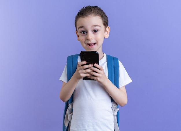 배낭을 메고 휴대전화를 들고 복사공간이 있는 보라색 벽에 격리된 카메라를 바라보는 어린 소년 프리미엄 사진