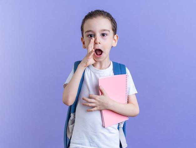 コピースペースで紫色の壁に隔離されたカメラのささやきを見て口の近くに手を保持しているメモ帳を保持しているバックパックを身に着けている感動の小さな男の子