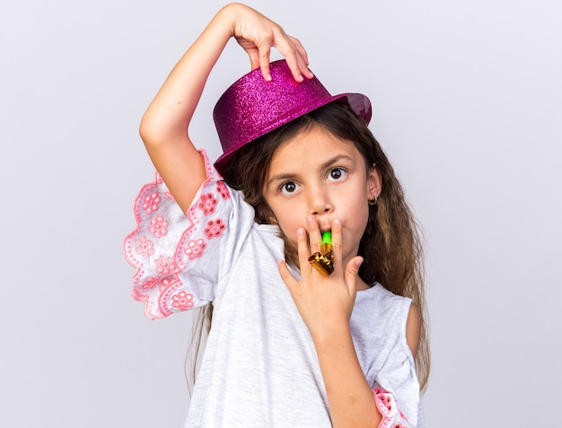 Impressed little caucasian girl with purple party hat blowing party whistle and putting hand on hat isolated on white wall with copy space
