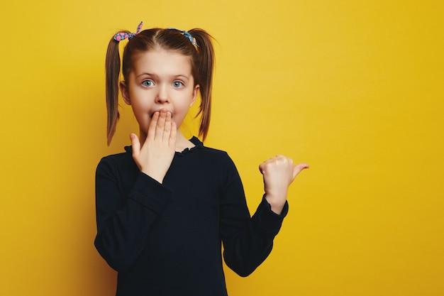 Впечатленный маленький милый ребенок указывает пальцем на пустое пространство, прикрытие немым ртом