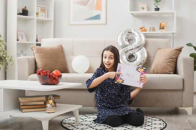 Impressed little girl on happy woman's day sitting on floor holding and points at postcard in living room