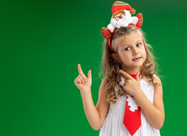 Impressed little girl wearing christmas hair hoop with tie points at behind isolated on green background