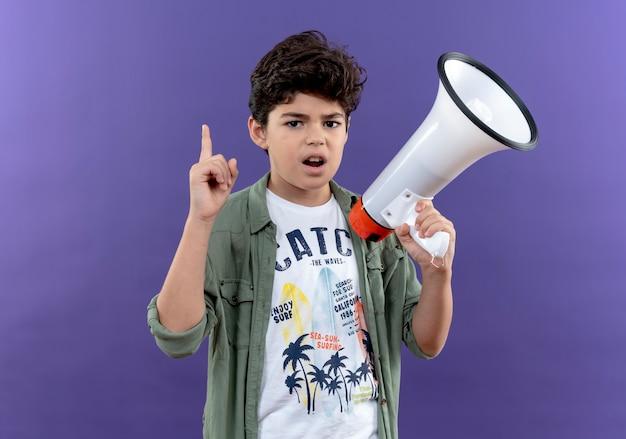 Piccolo scolaro impressionato che tiene altoparlante e indica in alto isolato sulla parete viola