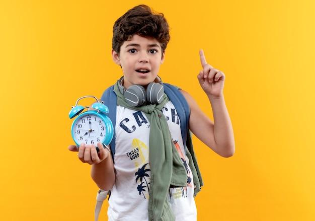 黄色の背景で隔離の目覚まし時計とポイントを保持しているバックバッグとヘッドフォンを身に着けている感動の小さな男子生徒