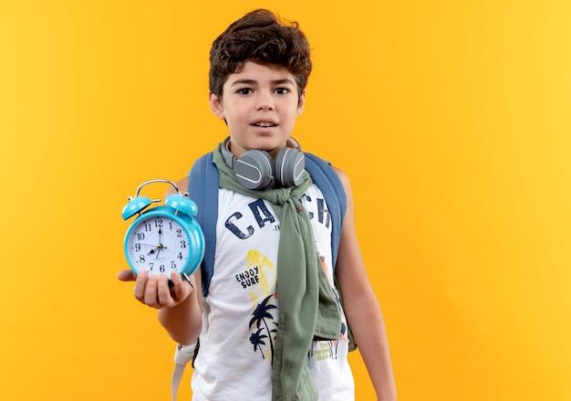 黄色の背景で隔離の目覚まし時計を保持しているバックバッグとヘッドフォンを身に着けている感動の小さな男子生徒