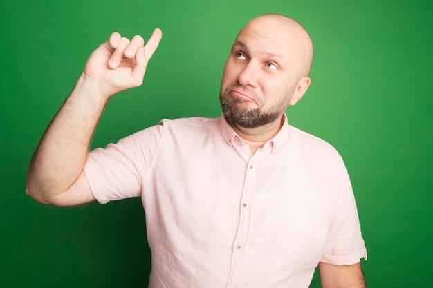 녹색에 고립 된 분홍색 티셔츠 포인트를 입고 측면 중년 대머리 남자를보고 감동