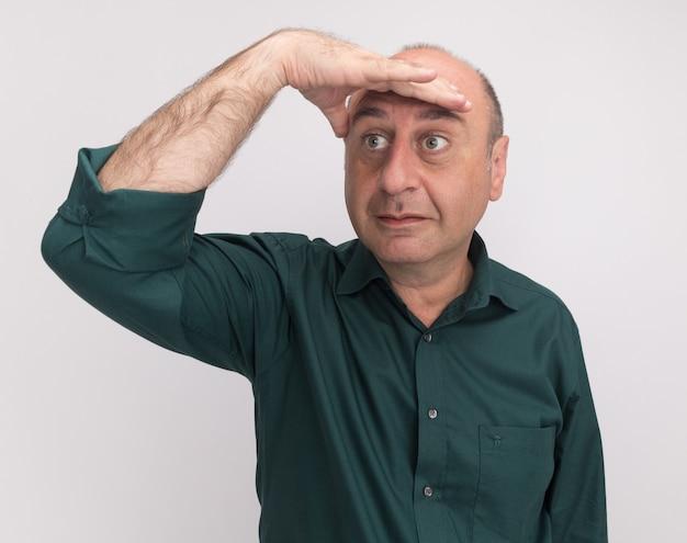 흰 벽에 고립 된 손으로 거리를보고 녹색 티셔츠를 입고 측면 중년 남자를보고 감동
