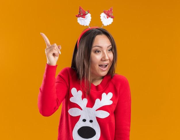 オレンジ色の壁に隔離された上にセーターポイントでクリスマスヘアフープを身に着けている側の若いアジアの女の子を見て感動