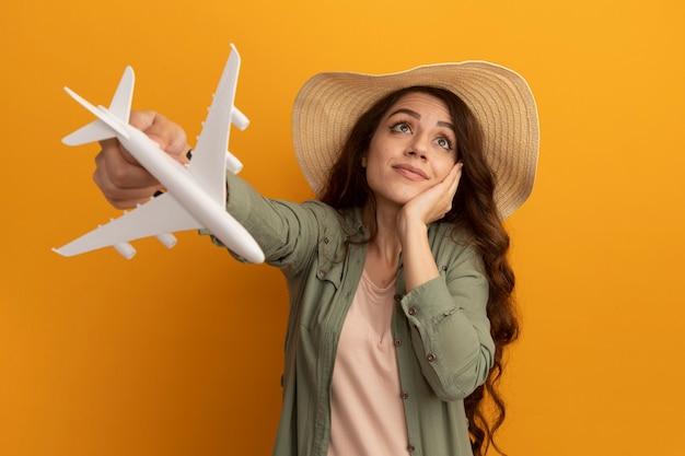 オリーブ グリーンの t シャツと黄色の壁に分離された頬に手を置いておもちゃの飛行機を保持している帽子を着ている美しい少女の側を見て感心