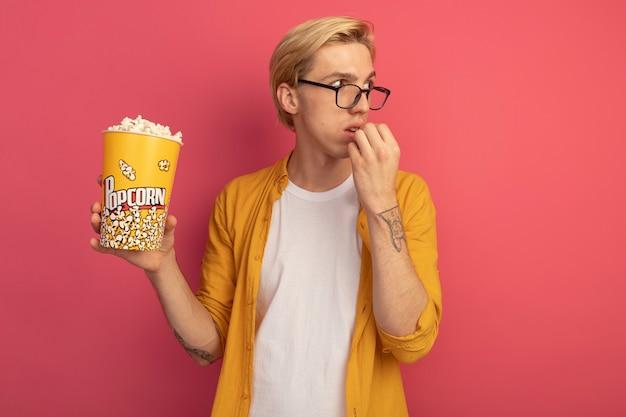 노란색 티셔츠와 안경을 착용하고 분홍색에 고립 된 팝콘 양동이를 시도하는 측면 젊은 금발의 남자를보고 감동