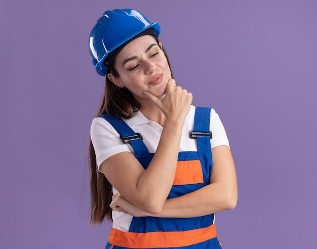 紫色の壁に孤立した制服を着た若いビルダーの女性が顎をつかんだ側を見て感銘を受けた