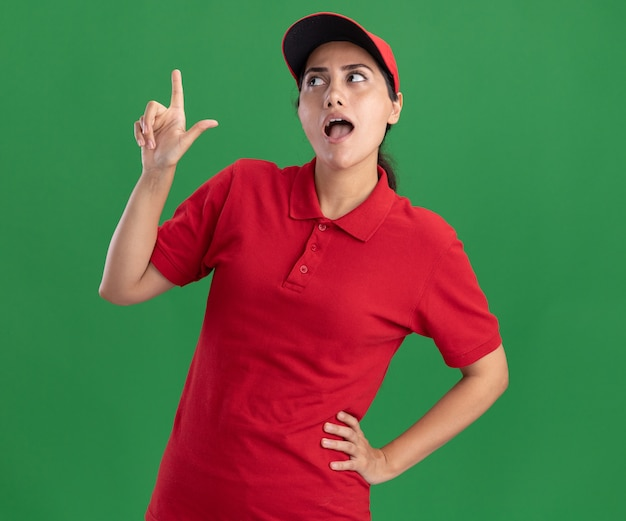 녹색 벽에 고립 된 엉덩이에 손을 넣어 위로 유니폼과 모자 포인트를 입고 측면 젊은 배달 소녀를보고 감동