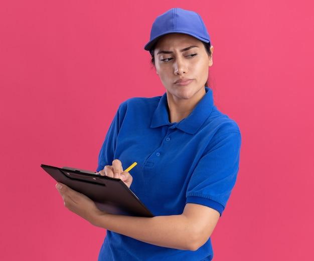 분홍색 벽에 고립 된 클립 보드에 뭔가 쓰는 모자와 유니폼을 입고 측면 젊은 배달 소녀를보고 감동