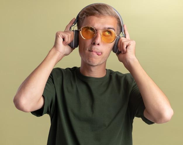 オリーブグリーンの壁に分離されたメガネとヘッドフォンで緑のシャツを着ている若いハンサムな男を見て感動