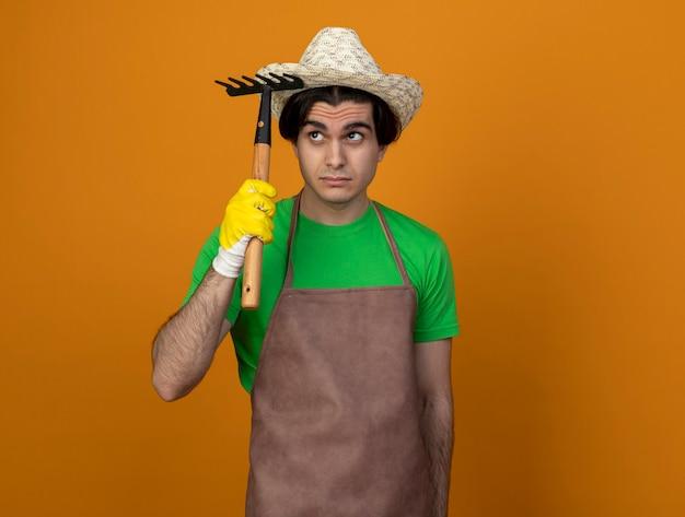 Впечатлен глядя на сторону молодого садовника-мужчину в униформе в садовой шляпе с перчатками, держащими грабли
