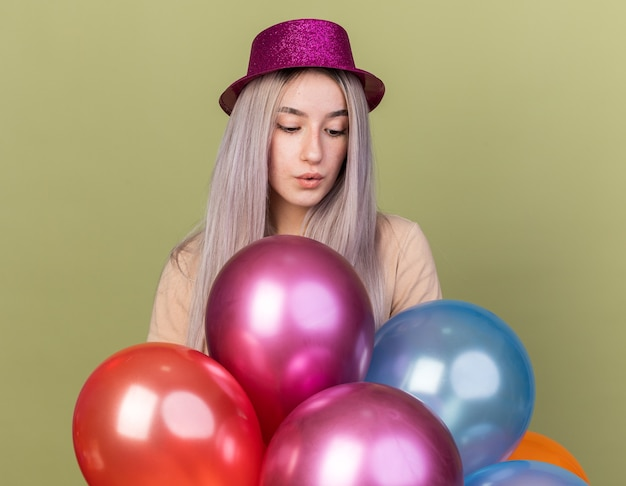 Impressed looking down young beautiful girl wearing party hat standing behind balloons