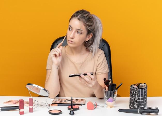 Впечатленная сторона молодая красивая девушка сидит за столом с инструментами для макияжа, держа палитру теней для век с кистью для макияжа, изолированной на оранжевой стене
