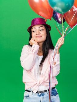 緑の壁に分離された頬に手を置いて風船を保持しているパーティーハットを身に着けている印象的な側面の若い美しい少女