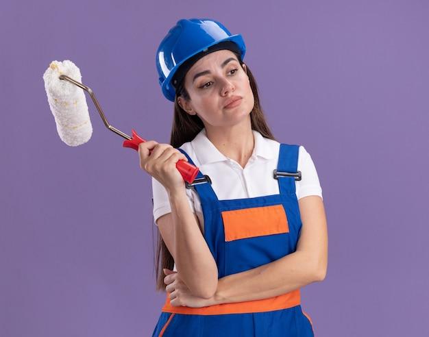 Impressionato guardando lato giovane donna costruttore in uniforme che tiene la spazzola a rullo isolata sulla parete viola