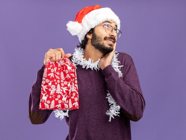 Impressed looking side young handsome guy wearing christmas hat with garland on neck holding christmas bag putting hand on cheek isolated on blue background