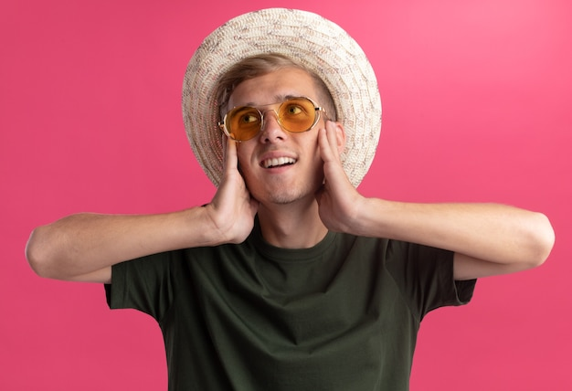 Impressionato guardando lato giovane bel ragazzo che indossa la camicia verde e occhiali con il cappello che mette le mani nelle guance isolate sul muro rosa