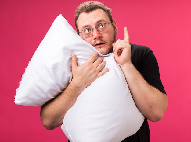 Impressed looking up middle-aged ill male hugged pillow points at up isolated on pink wall