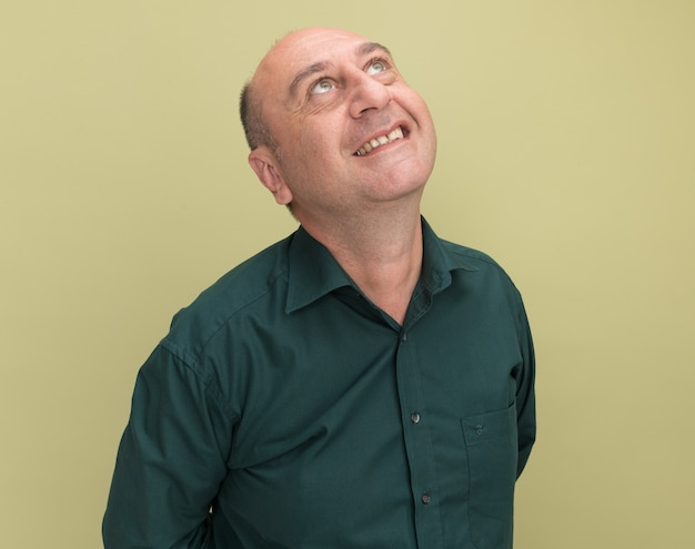 Impressed looking up middle-aged man wearing green t-shirt isolated on olive green wall