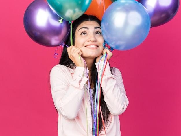 風船を持っている若い美しい女の子を見上げて感動
