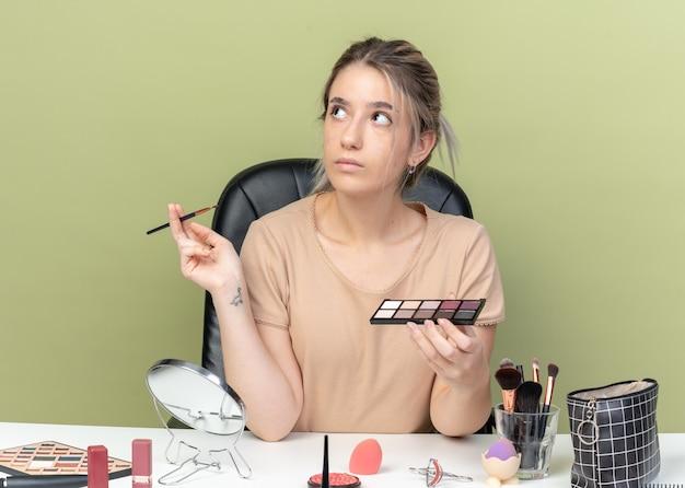 Под впечатлением от взгляда молодая красивая девушка сидит за столом с инструментами для макияжа, держа кисть с палитрой теней для век, изолированную на оливково-зеленой стене