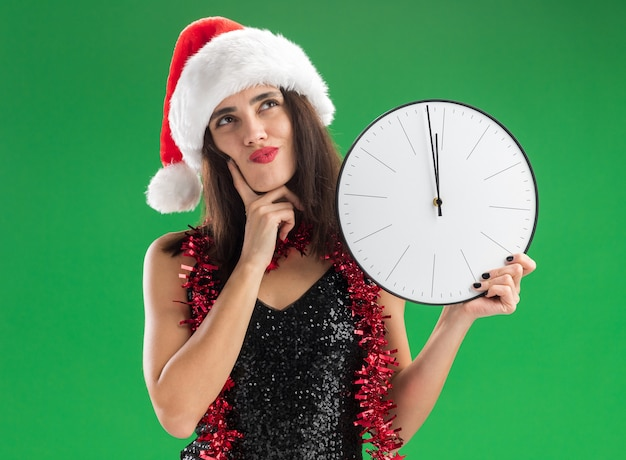 녹색 배경에 고립 뺨에 손가락을 넣어 벽 시계를 들고 목에 갈 랜드와 함께 크리스마스 모자를 쓰고 젊은 아름 다운 소녀를 찾고 감동
