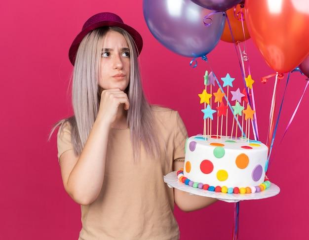 분홍색 벽에 격리된 케이크를 들고 풍선을 들고 파티 모자를 쓴 아름다운 소녀를 올려다보는 것에 깊은 인상을 받았습니다.