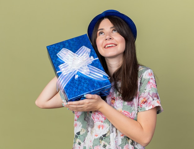 Impressed looking up young beautiful girl wearing party hat holding gift box around face isolated on olive green wall