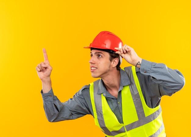Впечатлен глядя вверх молодой строитель в форме указывает на вверх