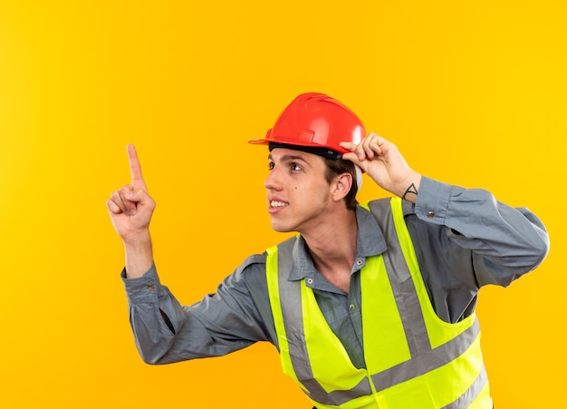 Impressionato guardando il giovane costruttore in uniforme punta verso l'alto