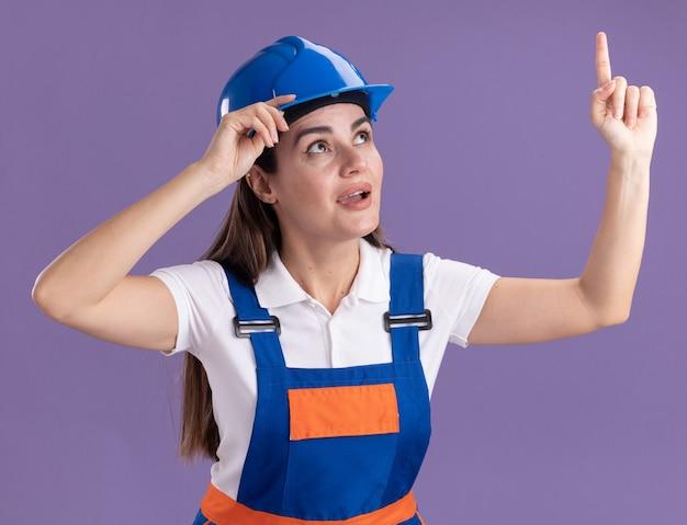 Impressionato guardando la giovane donna del costruttore in punti uniformi in alto isolato sul muro viola