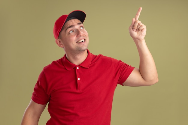 올리브 녹색 벽에 고립 된 유니폼과 모자 포인트를 입고 젊은 배달 남자를 찾고 감동