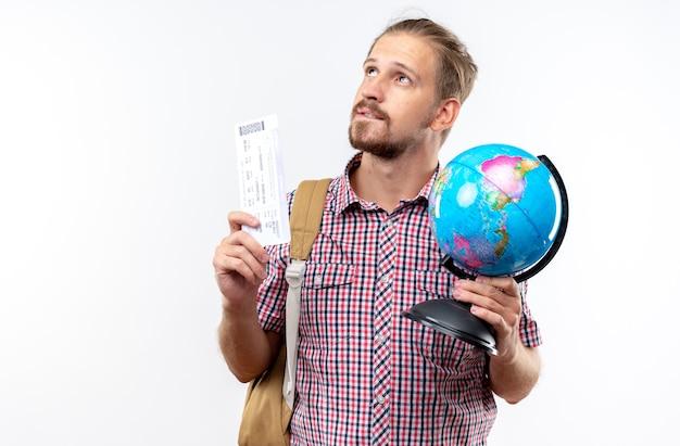チケットと地球儀を保持しているバックパックを身に着けている若い男の学生を探して感動