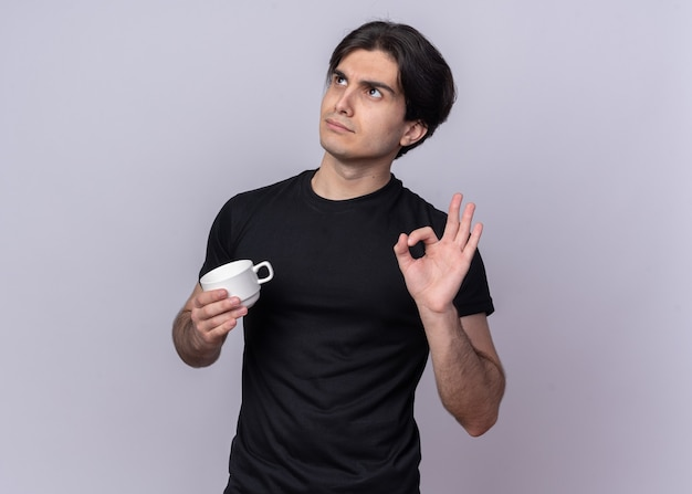 Под впечатлением от взгляда молодого красивого парня в черной футболке с чашкой кофе, держащего чашку кофе, изолированного на белой стене