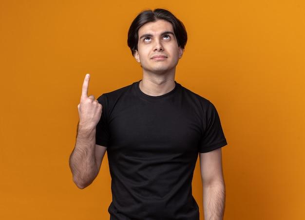 오렌지 벽에 고립 된 검은 티셔츠 포인트를 입고 젊은 잘 생긴 남자를 찾고 감동