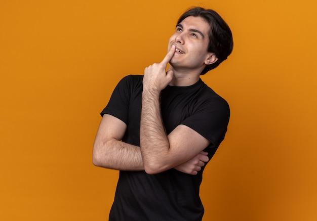 オレンジ色の壁に隔離された口に指を置く黒いtシャツを着ている若いハンサムな男を見上げて感動